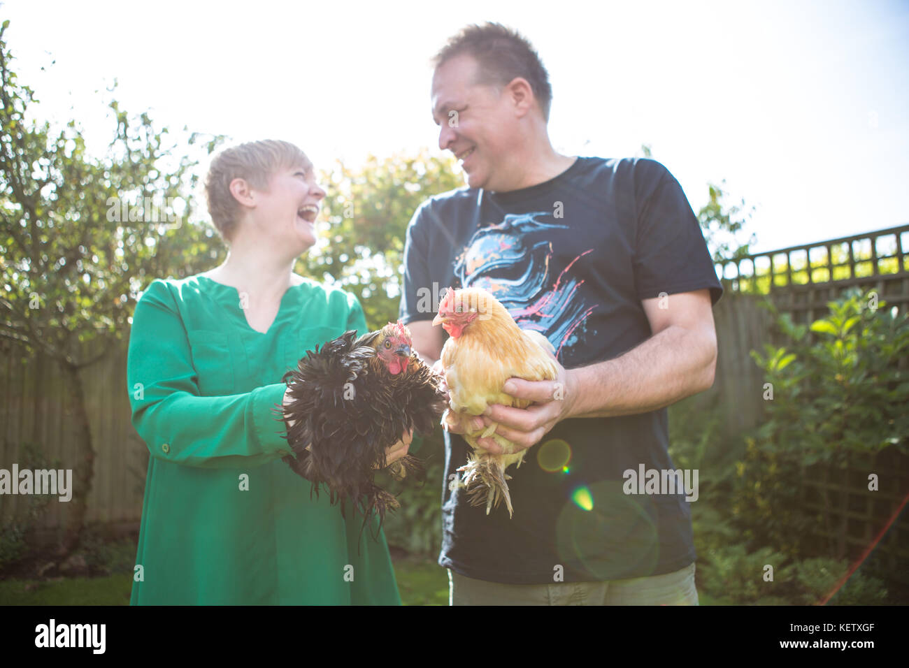 Young couple with their bantam chicken pets - Stock Image