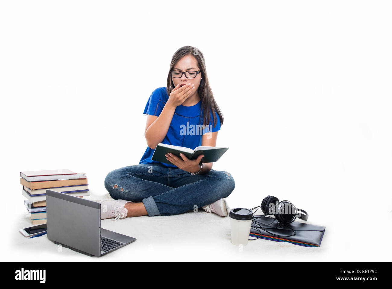Student girl sitting studding and yawning like being tired with books and coffee around isolated on white background - Stock Image