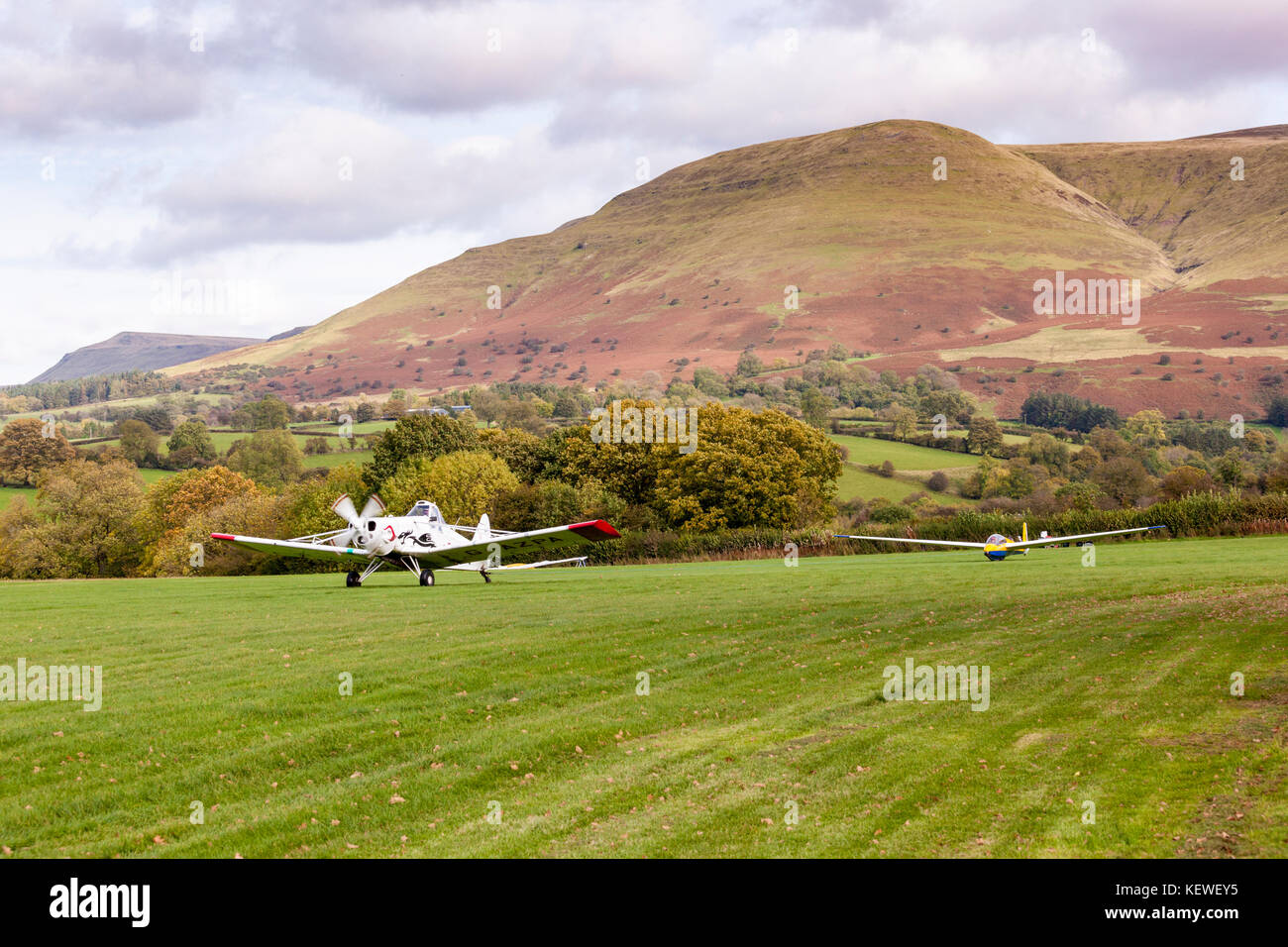A glider being towed up by tug at the Black Mountains Gliding Club on the Brecon Beacons near Talgarth, Powys, Wales - Stock Image