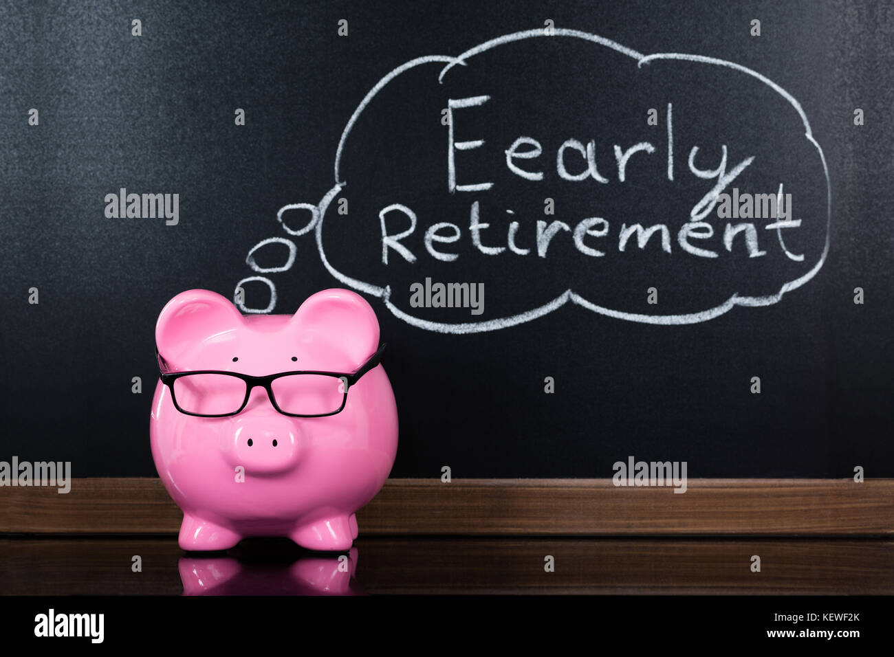 Close-up Of Piggybank With Retirement Concept On Blackboard - Stock Image