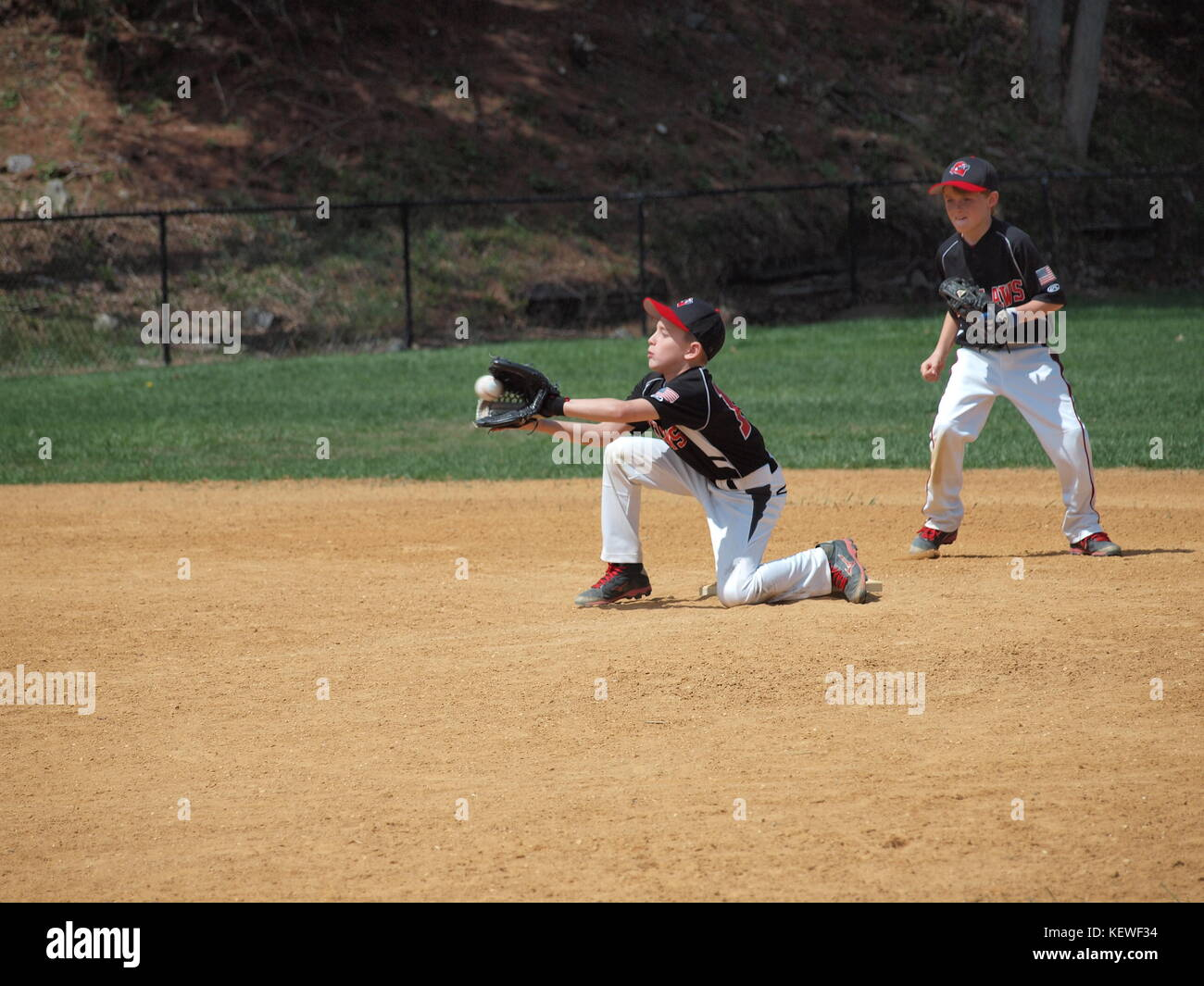 Little League fielder stopping ball during hot summer day. Stock Photo