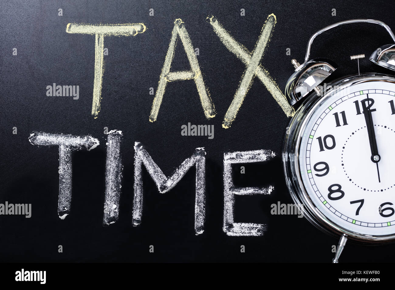 Close-up Of An Alarm Clock Near Tax Time Concept On Blackboard - Stock Image