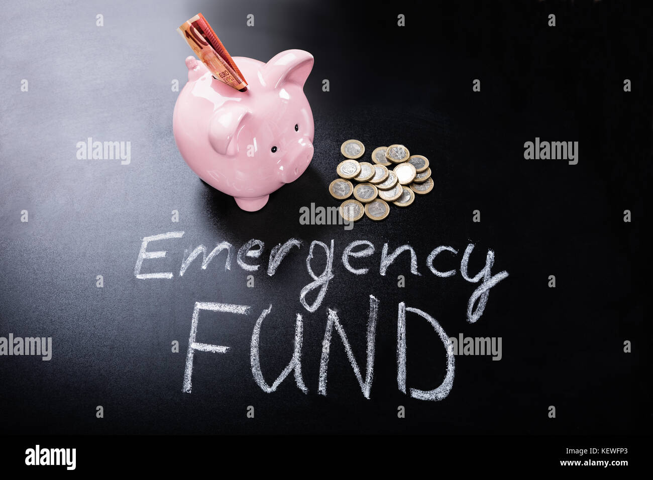 Emergency Fund Text In Front Of Piggybank With Banknotes And Coins - Stock Image