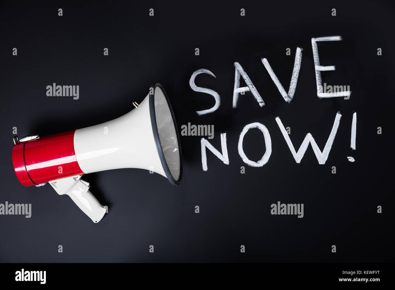 Close-up Of Save Now Speech Through Loudspeaker On Blackboard - Stock Image