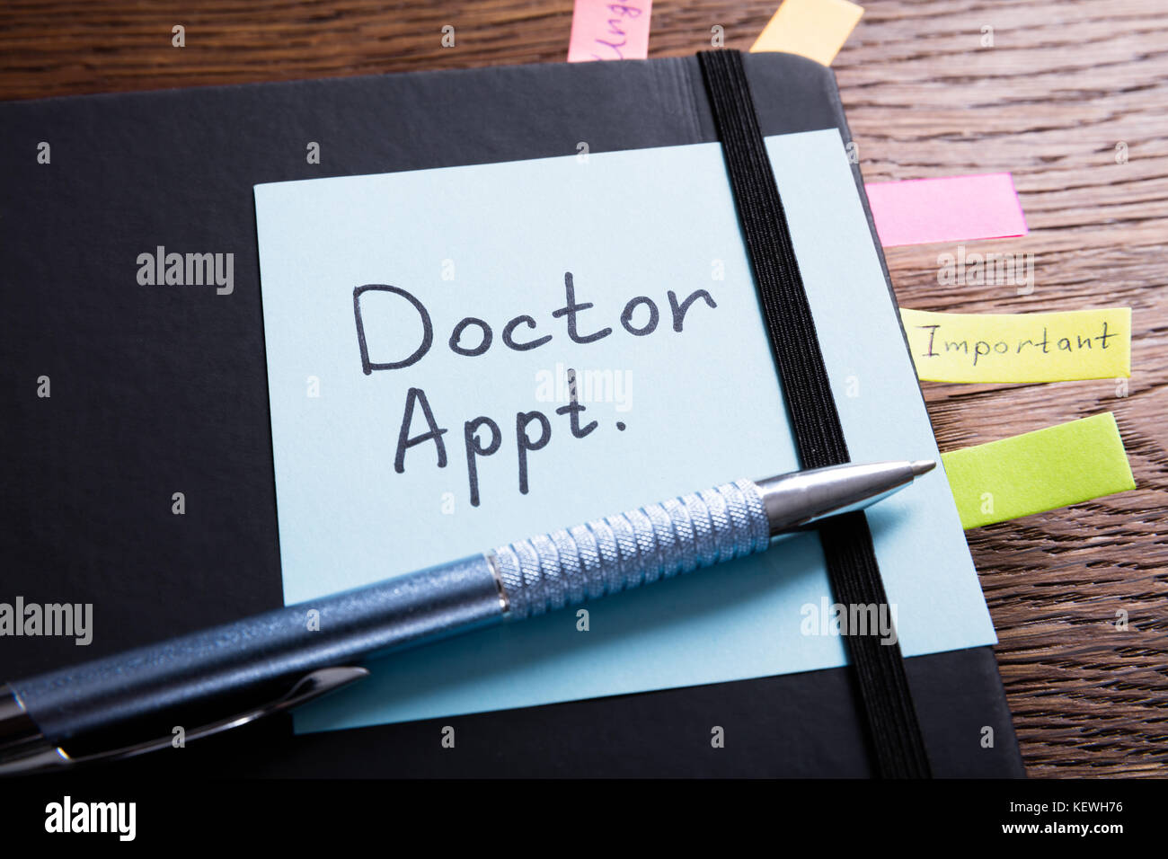 High Angle View Of A Diary Of Doctor Appointment With Sticky Note On Desk - Stock Image
