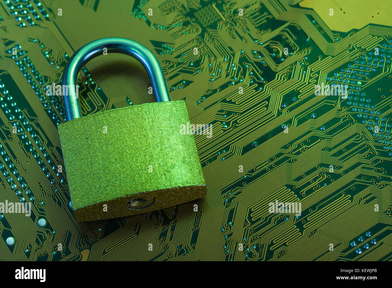 Macro-photo of small padlock on an an electronic circuitboard - metaphor for cyber security, data breach, hacking,secure - Stock Image