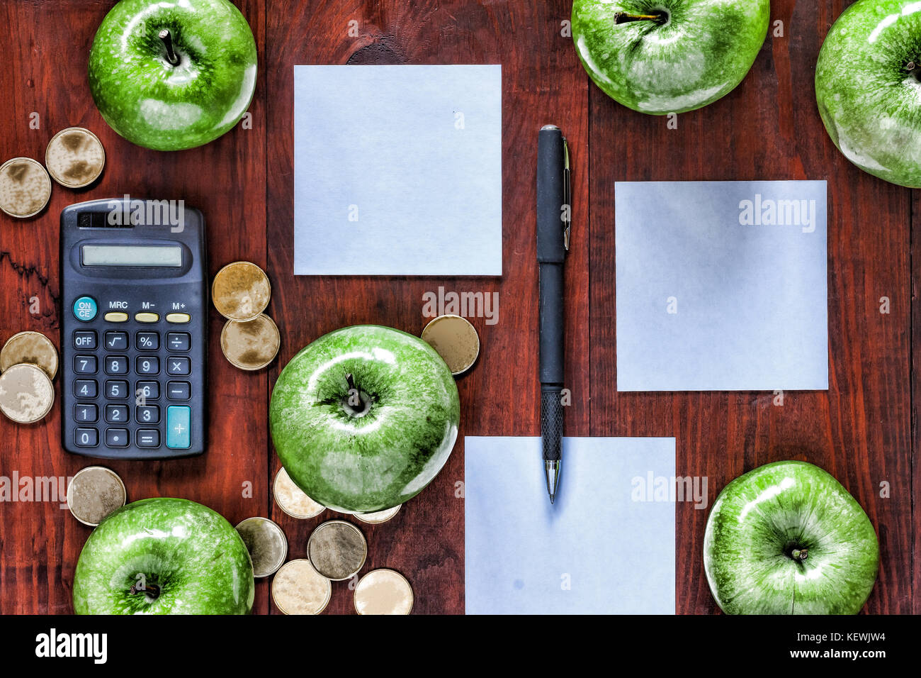 Concept: business, investment, enrichment, logistics, planning.   Green apples, gold coins, calculator and paper - Stock Image