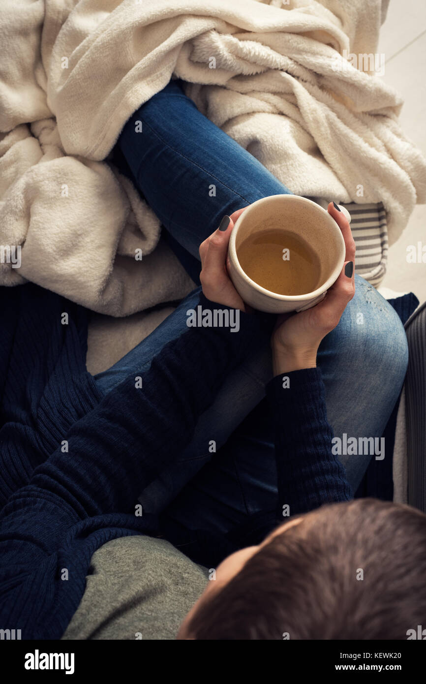 Young woman at home sitting in comfy armchair and drinking tea, view from above - Stock Image