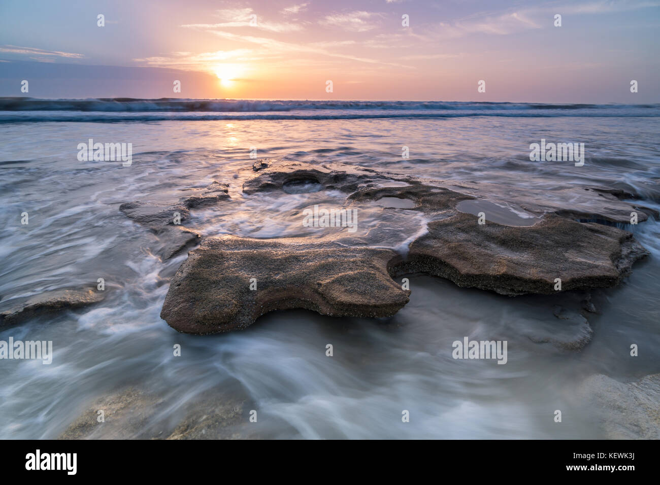 Sunrise over the Incoming tide swirling around a coquina rock at Marineland Beach, Florida - Stock Image