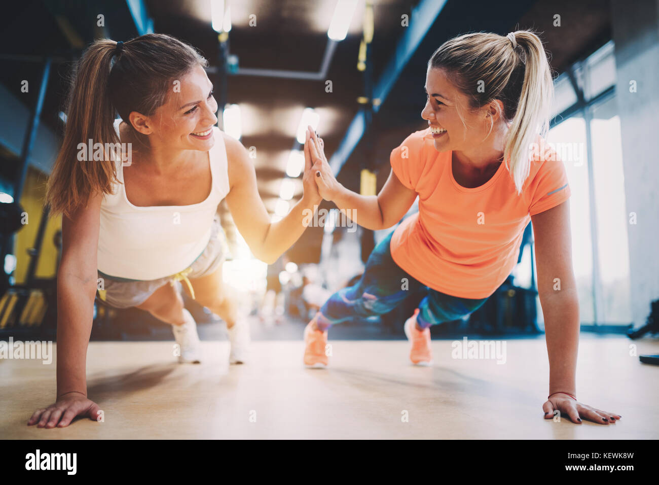 Two sporty girls doing push ups in gym - Stock Image