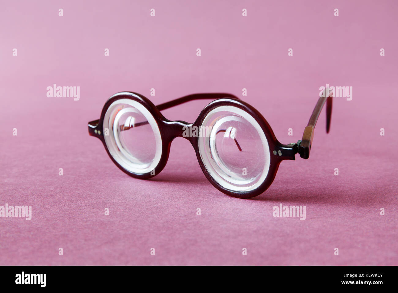 Old fashion design spectacles eyeglasses on pink violet paper background. Vintage style men fashion accessories Stock Photo