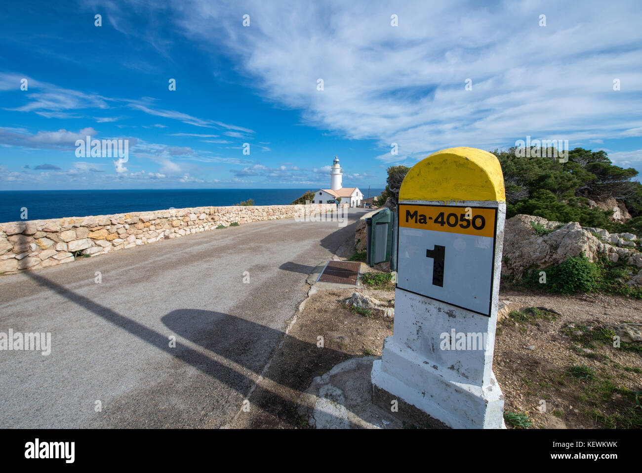 SPAIN, BALEARIC, MALLORCA: milestone and lighthouse Capdepera at the north-eastern cape of Mallorca bounded by a - Stock Image