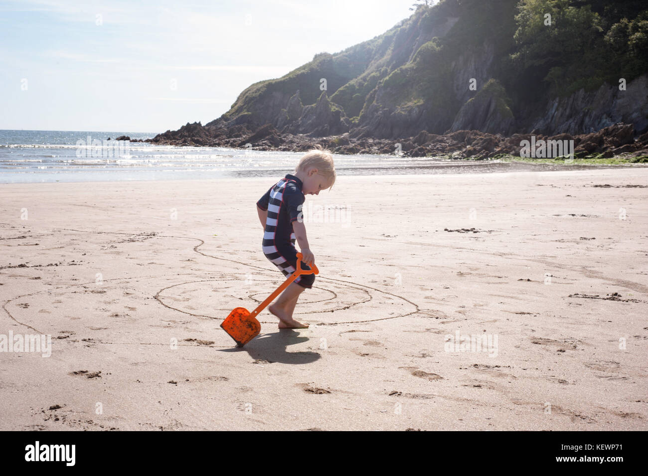Young boy splashing in the sea and drawing in sand Stock Photo