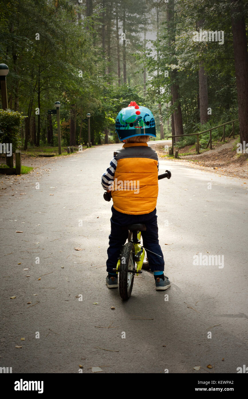 Little boy riding a bike down a forest path - Stock Image