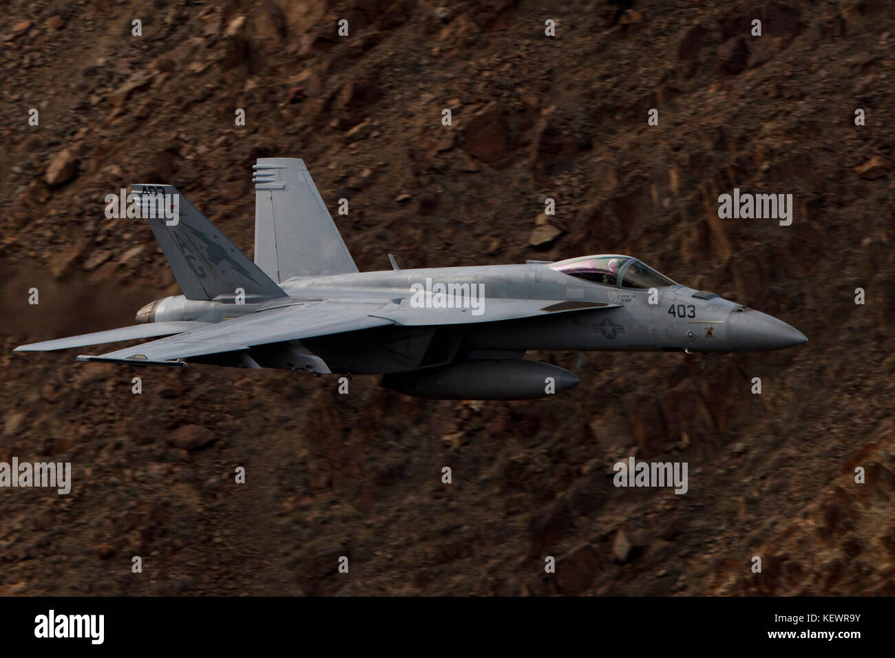 Boeing F/A-18E Super Hornet from United States Navy squadron VFA-25 Fist of the Fleet (AG 403) flies low level through Stock Photo