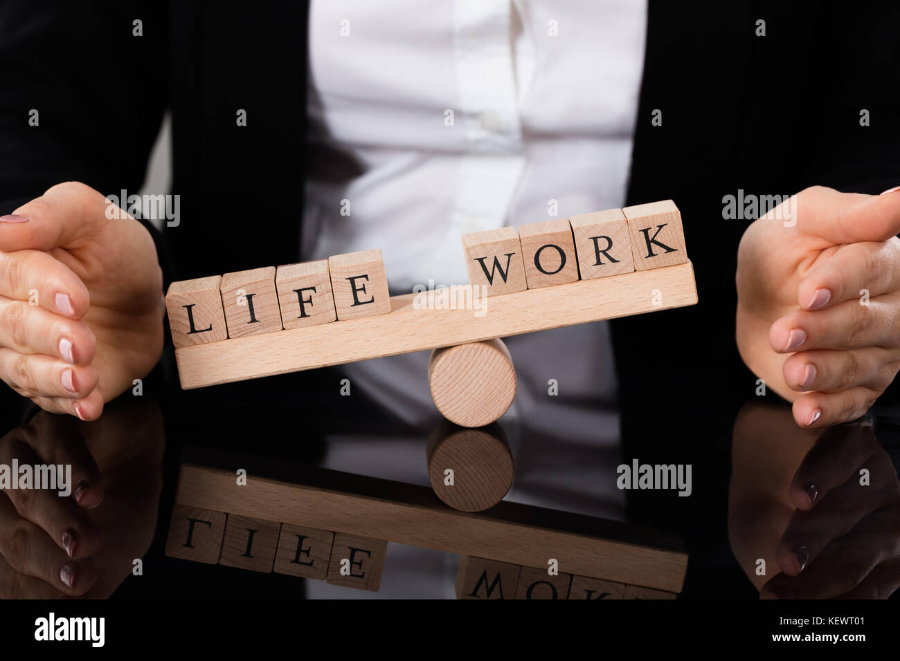 Businesswoman Hand Covering Balance Between Life And Work On Seesaw At Table - Stock Image
