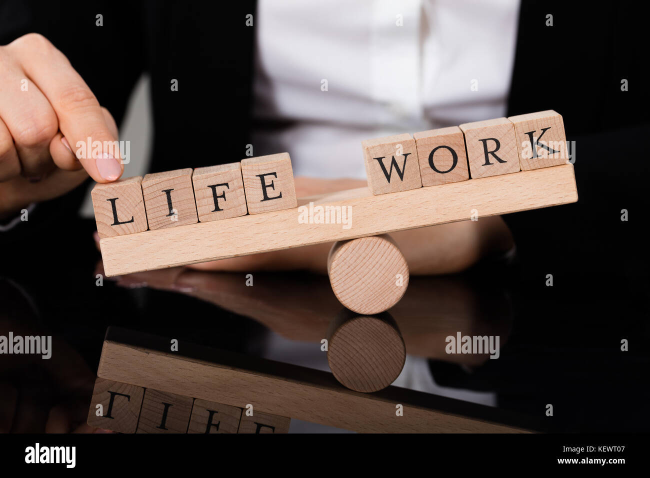 Close-up Of A Person Showing Imbalance Between Life And Work On Seesaw - Stock Image