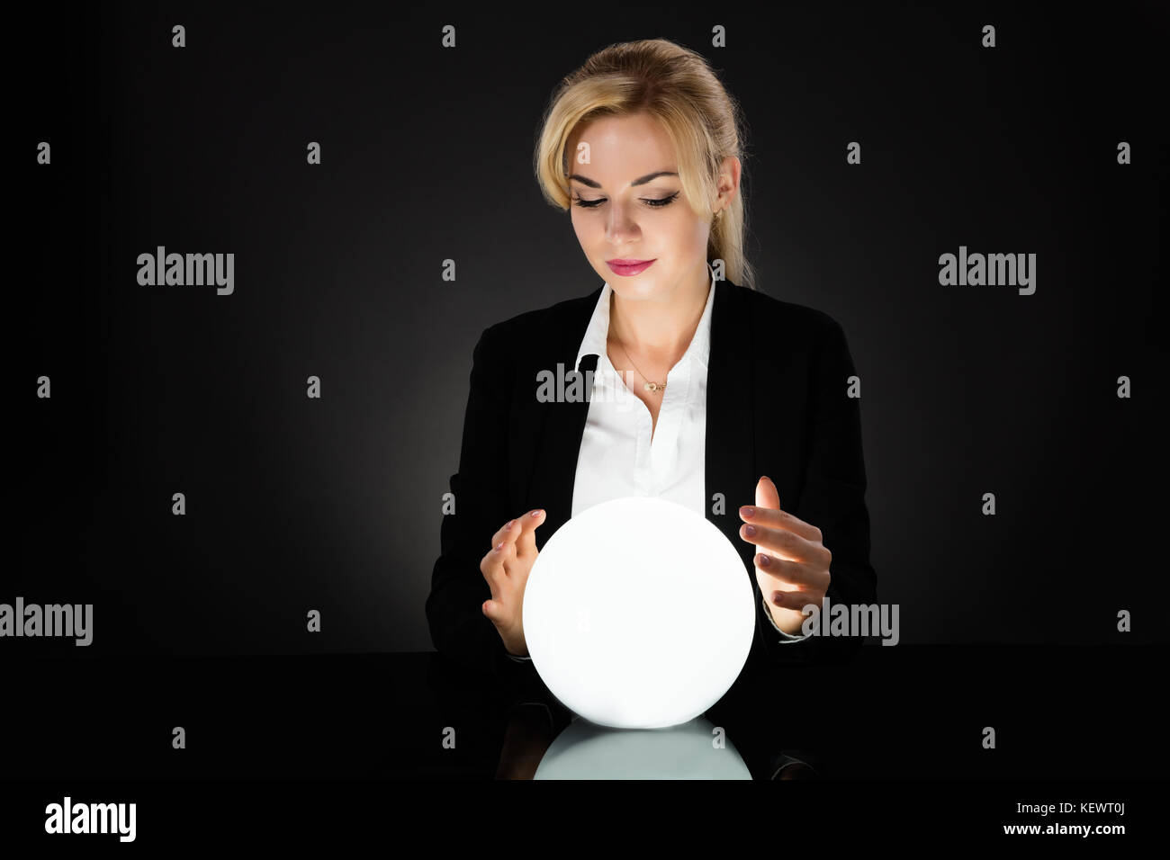 Businesswoman Looking Into The Future In A Crystal Ball On Black Background. Fortune Teller Predicting Future - Stock Image