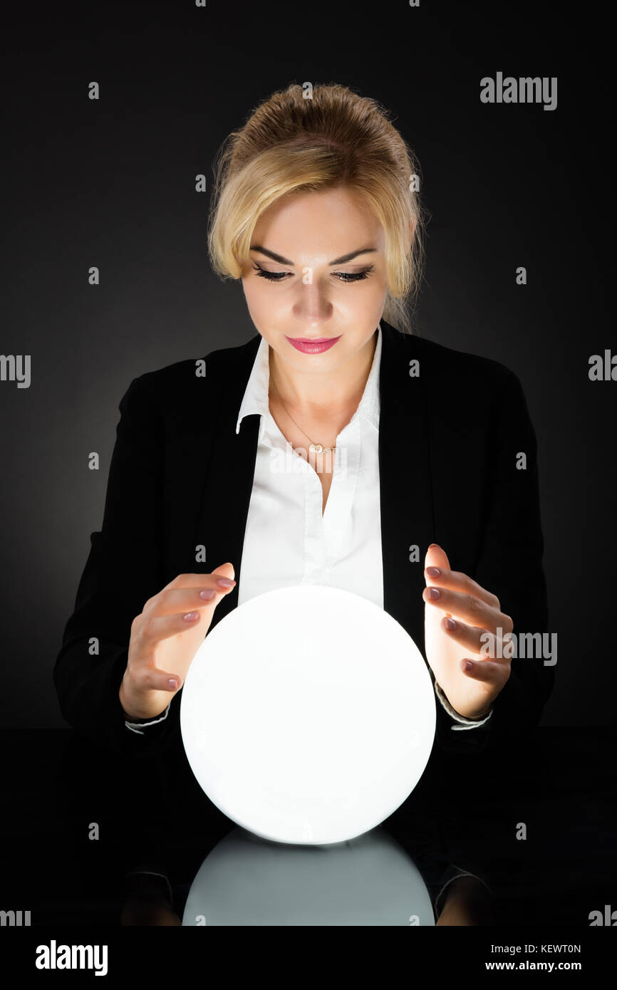 Young Businesswoman Looking Into The Future In A Crystal Ball On Black Background. Fortune Teller Predicting Future - Stock Image