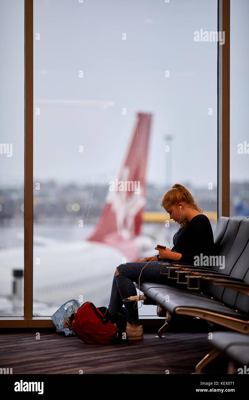 Boston Massachusetts New England North America USA , Logan International Airport airside passenger at window Virgin - Stock Image
