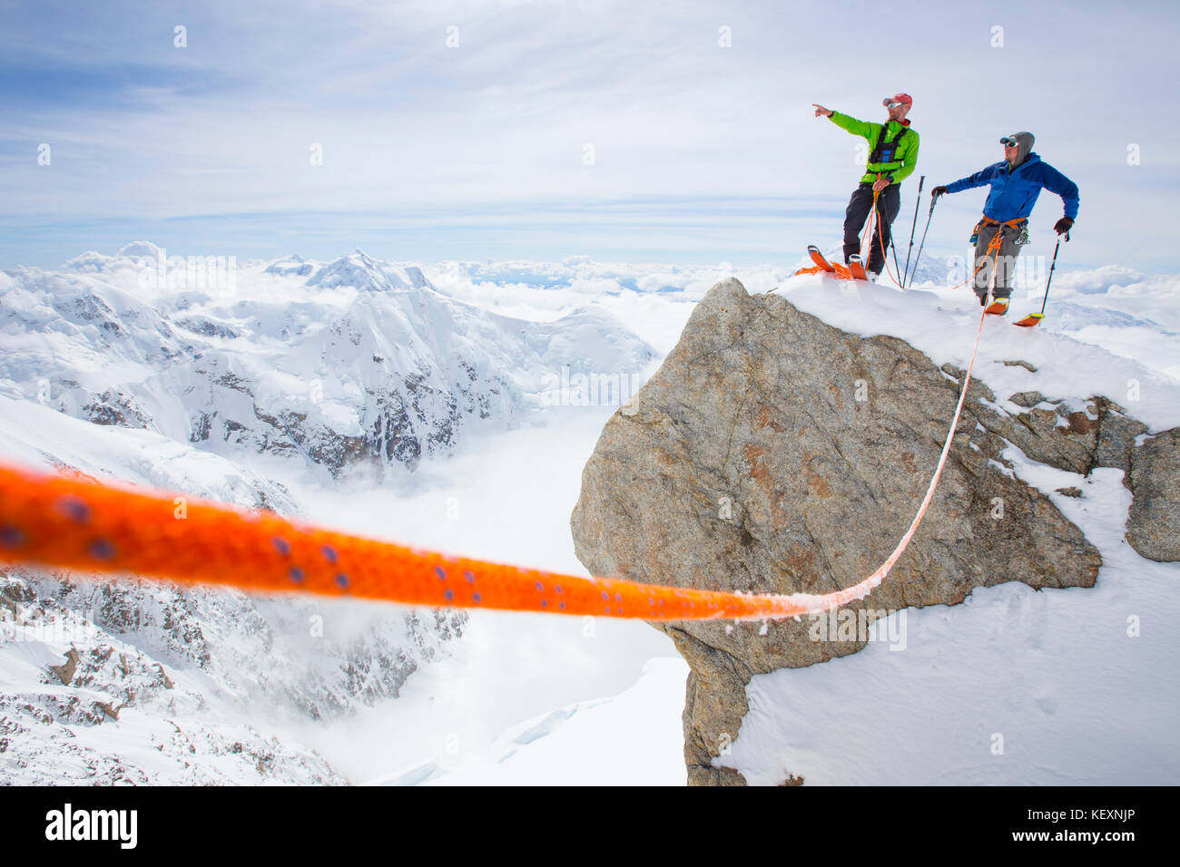 Two ski mountaineers are standing on a summit in Denali National Park. One is pointing the way to his buddy. A safety - Stock Image