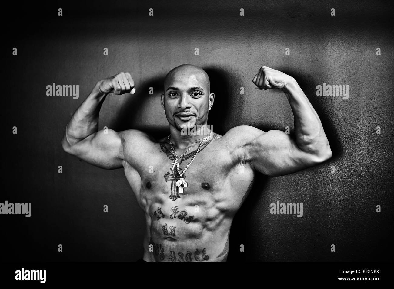 Black and white studio portrait of shirtless bodybuilder flexing muscles, Taunton, Massachusetts, USA - Stock Image