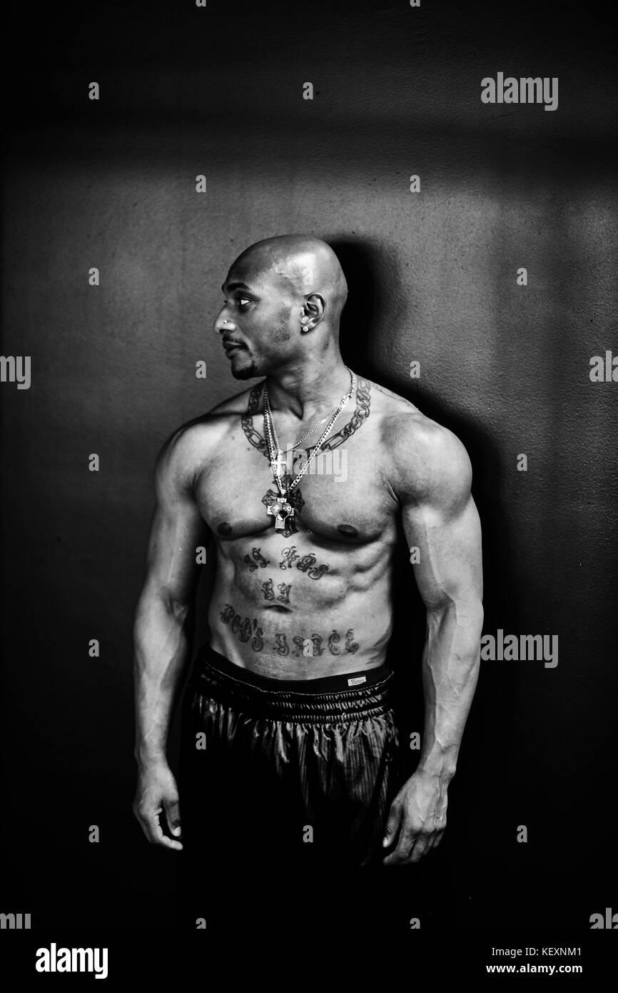 Black and white studio portrait of shirtless bodybuilder standing and looking away, Taunton, Massachusetts, USA - Stock Image