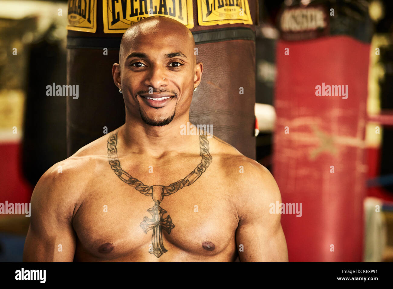 Portrait of boxer standing against punching bag and smiling, Taunton, Massachusetts, USA - Stock Image