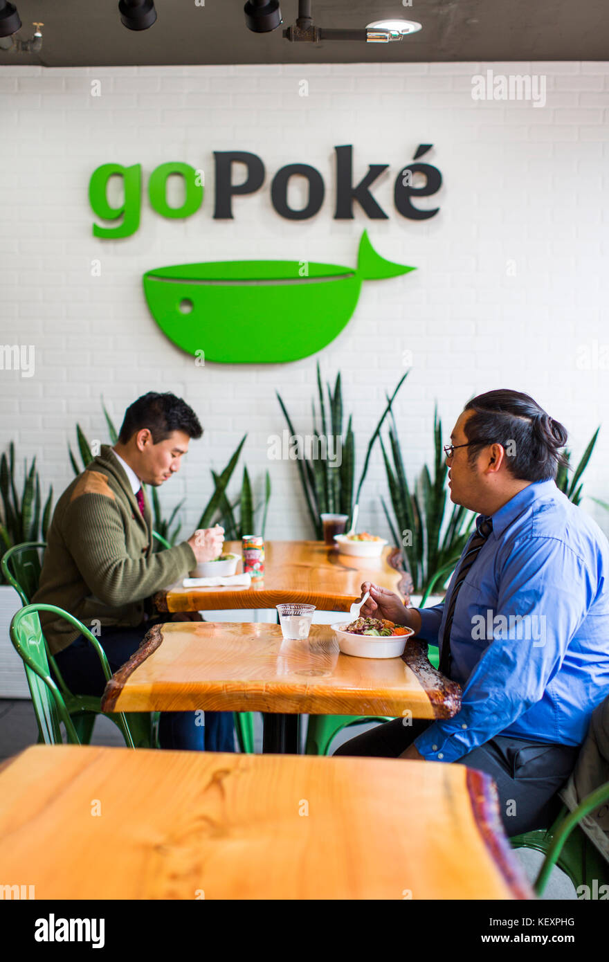 Photograph of two male customers at restaurant eating poke, traditional Hawaiian dish, Seattle, Washington State, - Stock Image