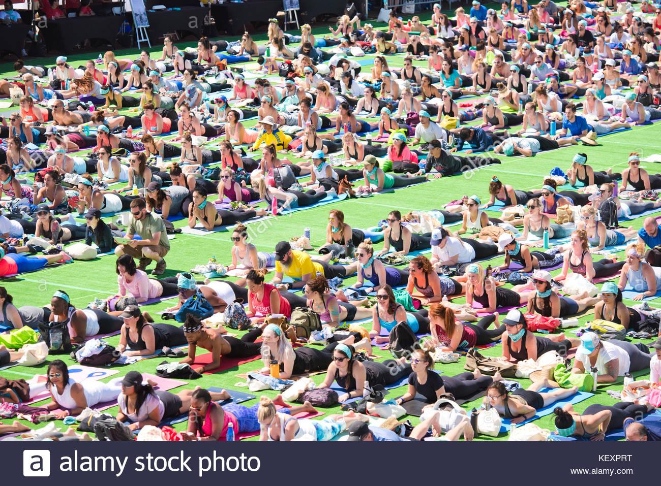 People performing sphinx pose during outdoor yoga festival on Santa Monica Pier in Santa Monica, California, USA - Stock Image