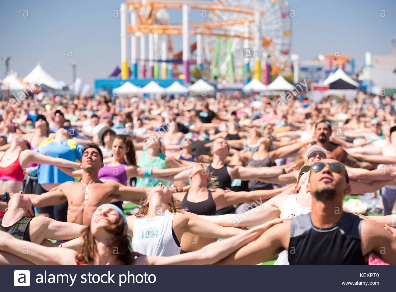 People stretching during outdoor yoga festival on Santa Monica Pier in Santa Monica, California, USA - Stock Image