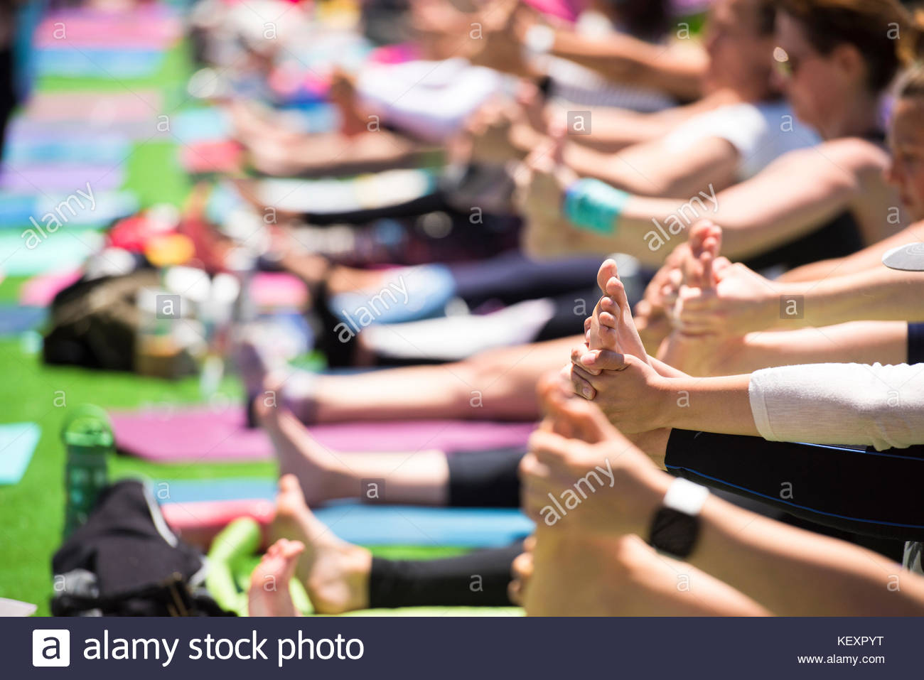 Close up of people hands and feet doing happy baby pose during outdoor yoga festival in Santa Monica, California, - Stock Image