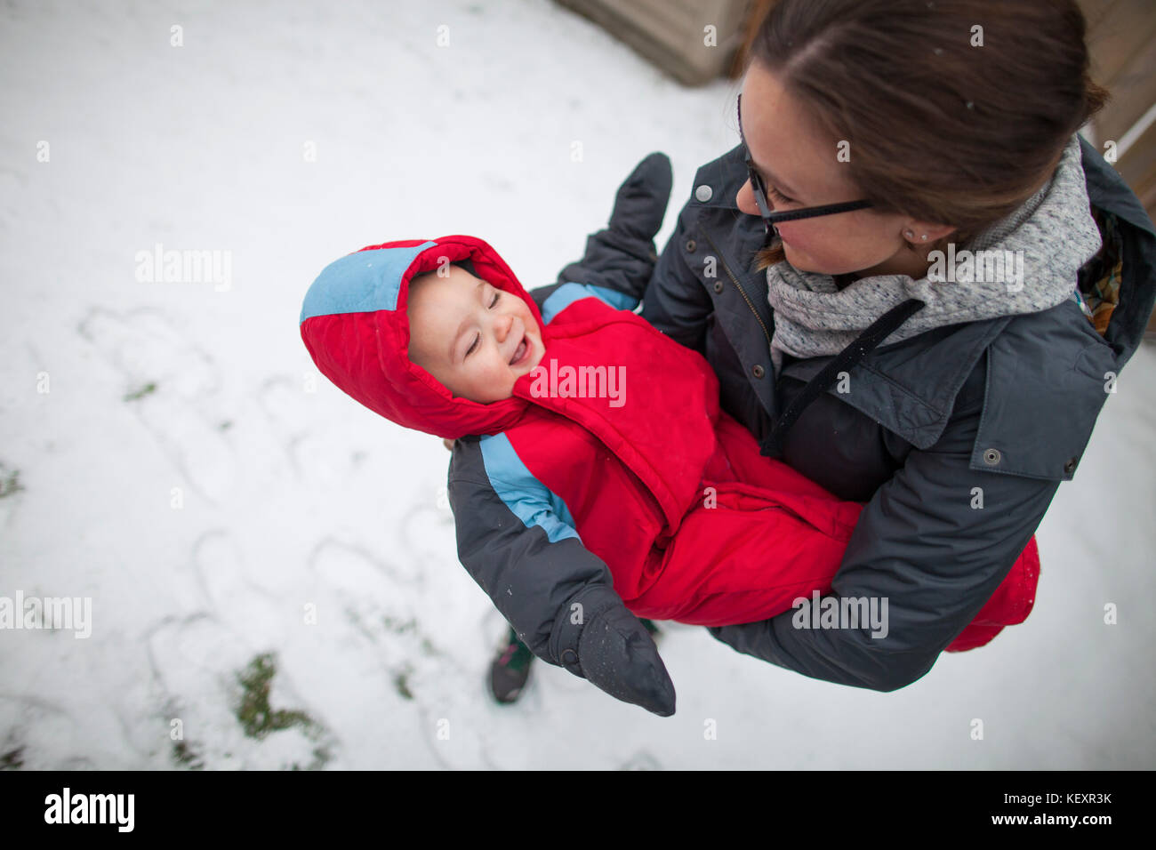 Mother holding laughing baby outdoors in winter while wearing warm clothing, Langley, British Columbia, Canada - Stock Image