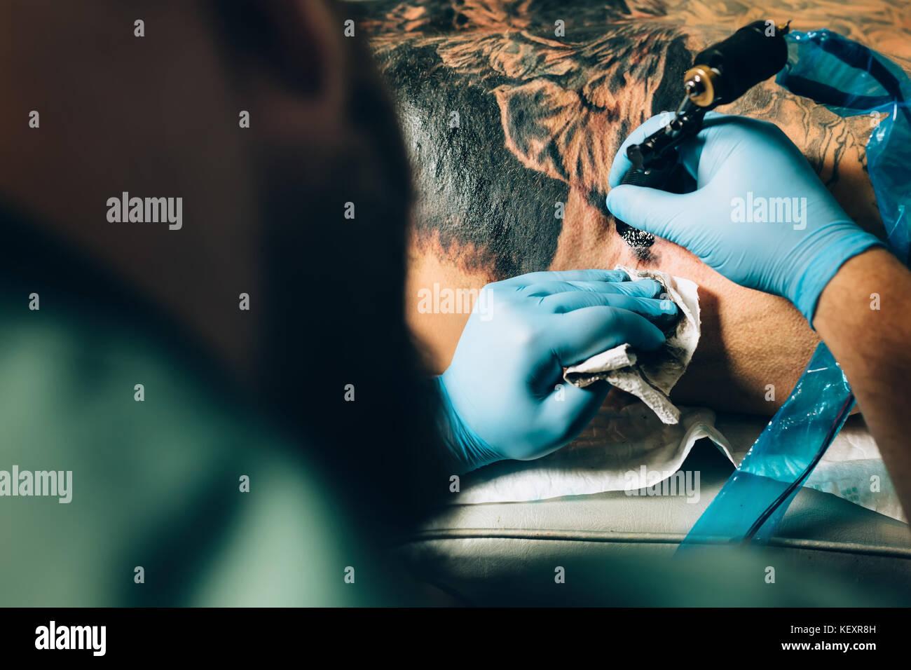 tattoo master artist makes a tattoo. Closeup - Stock Image