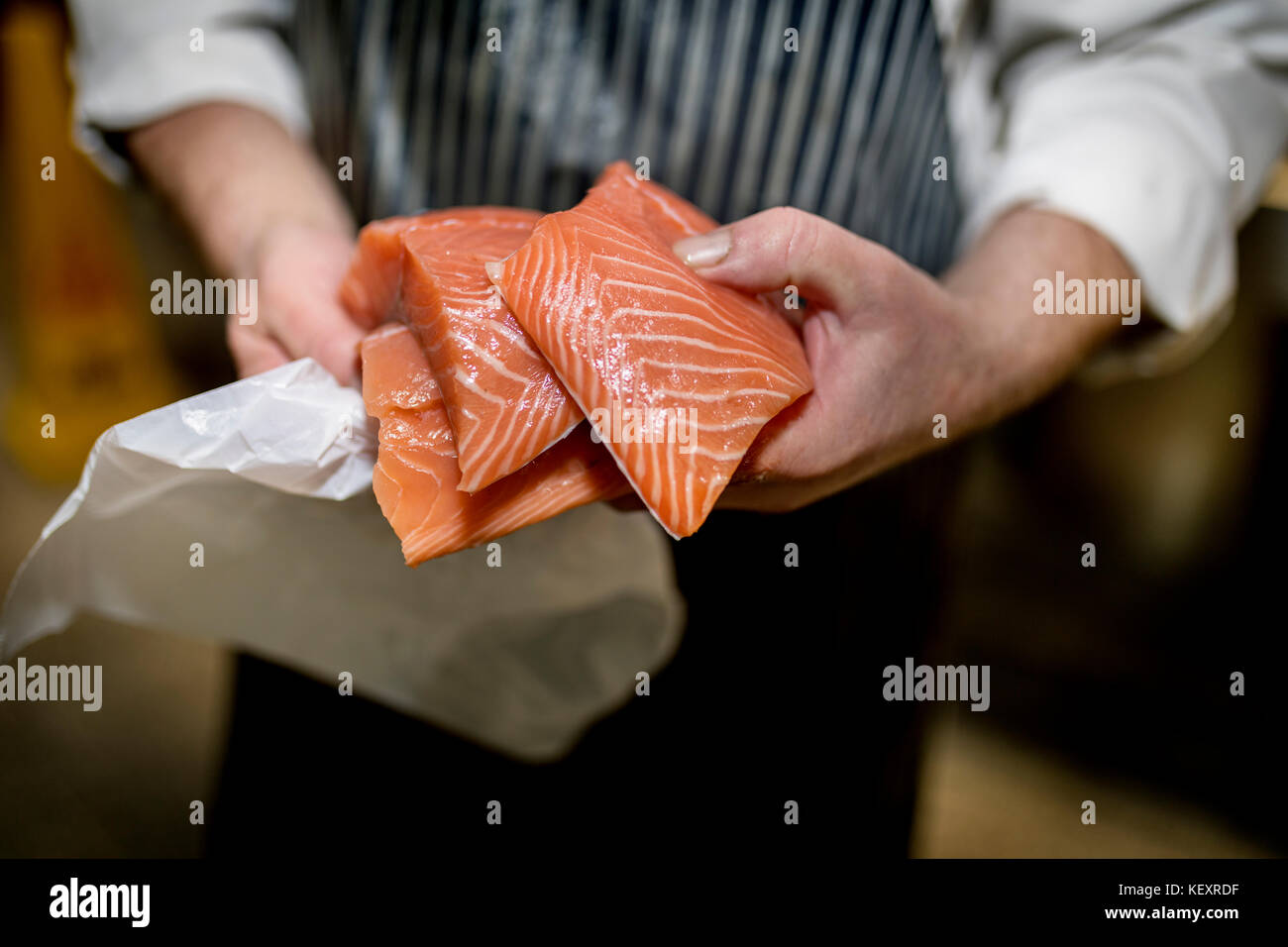Close up of a fish monger's hands holding three fillets of fresh filleted salmon on a market stall in Yorkshire, - Stock Image