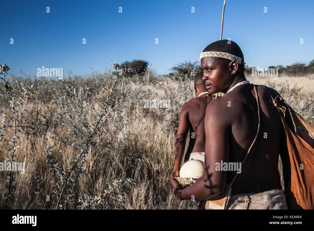 Photograph of two members of San people walking through underbrush in Kalahari Desert, Botswana - Stock Image