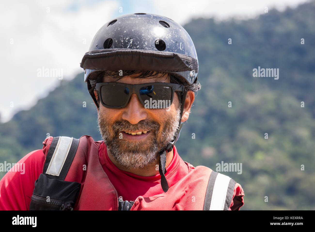 Man with helmet smiles while on a river expedition in Manu National Park, Peru. - Stock Image