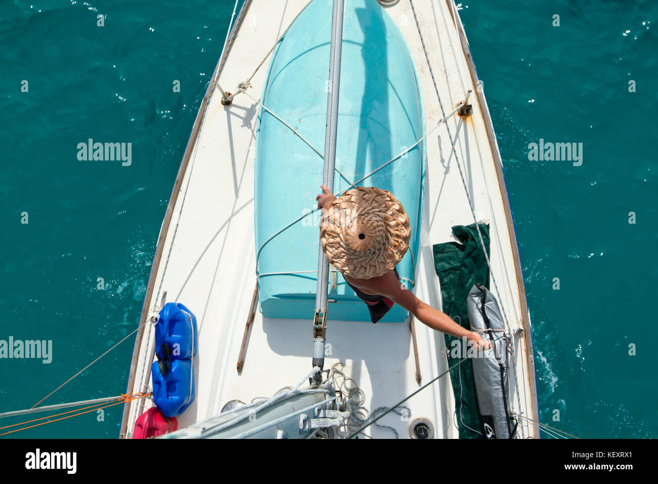 A man leans against the rigging as seen from above after wrapping the sail off Glovers Reef on the coast of Belize. - Stock Image
