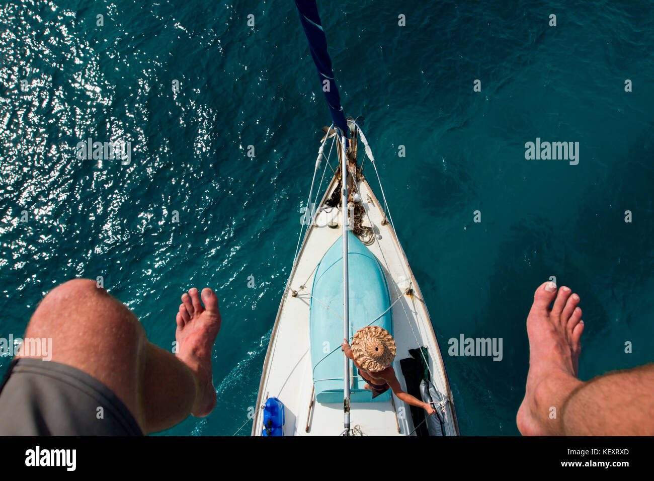 A man leans against the rigging as seen from above and framed by a man's feet on the mast after wrapping the - Stock Image