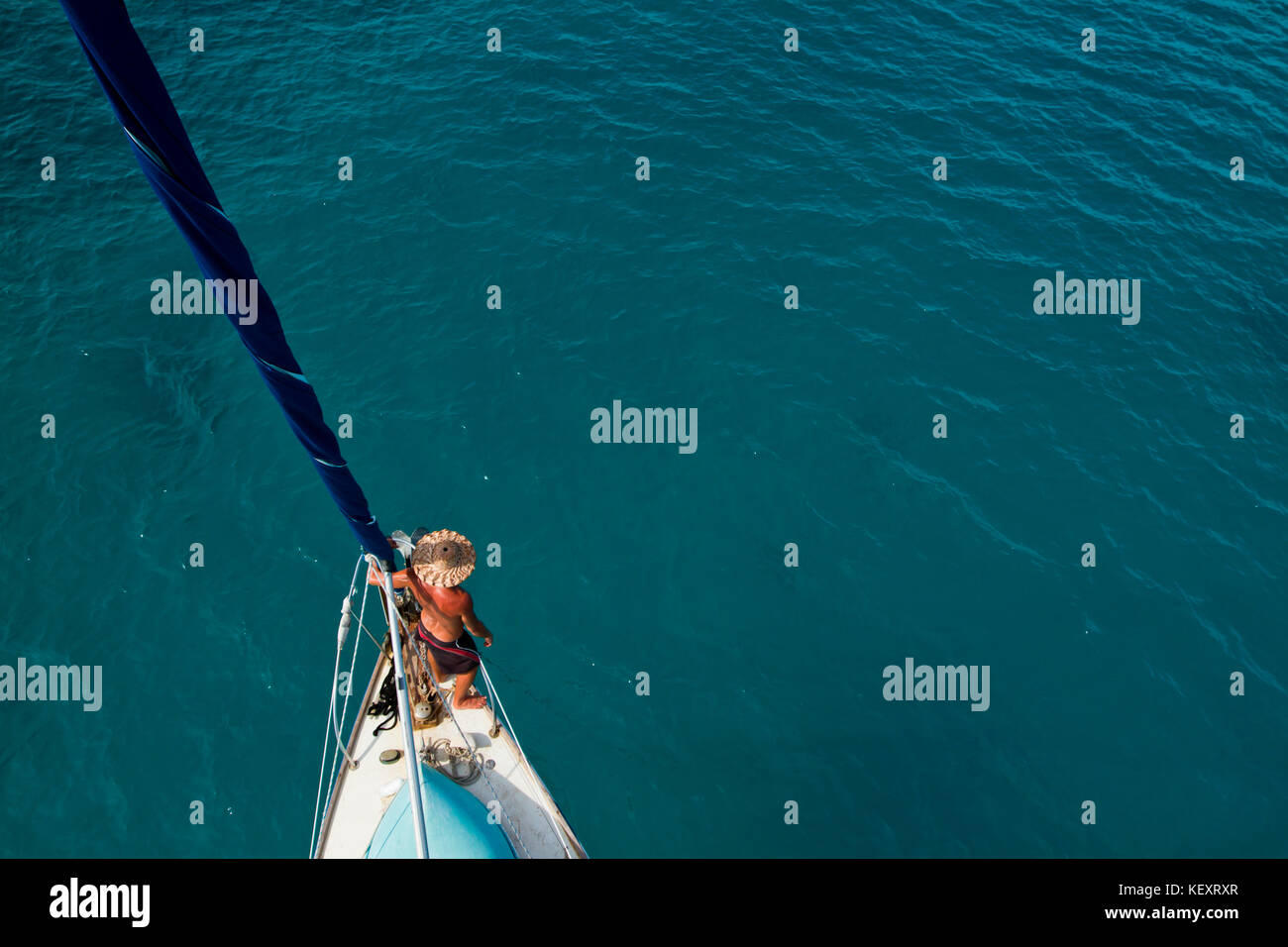 A man leans against the headstay and mainsail as seen from above after wrapping the sail off Glovers Reef on the - Stock Image