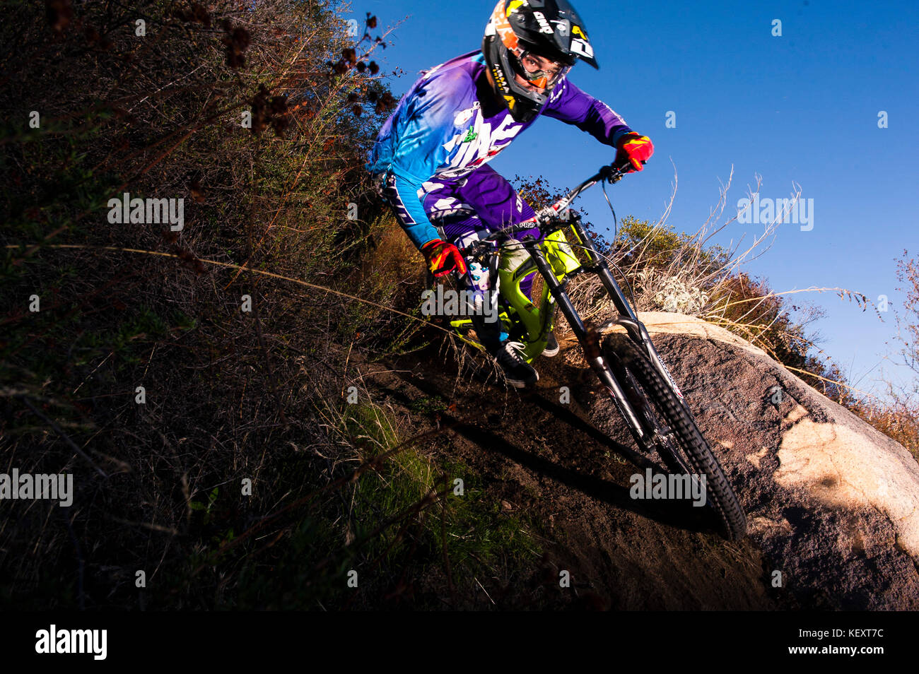 Cody Warren uses a rock to finds traction in a turn while riding his Downhill bike in Southern Califonia. December - Stock Image