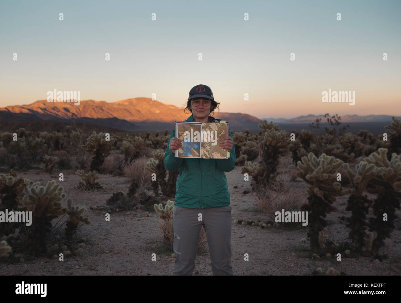 Portrait of woman standing in Chollah Cactus Garden and holding guidebook, California, USA Stock Photo