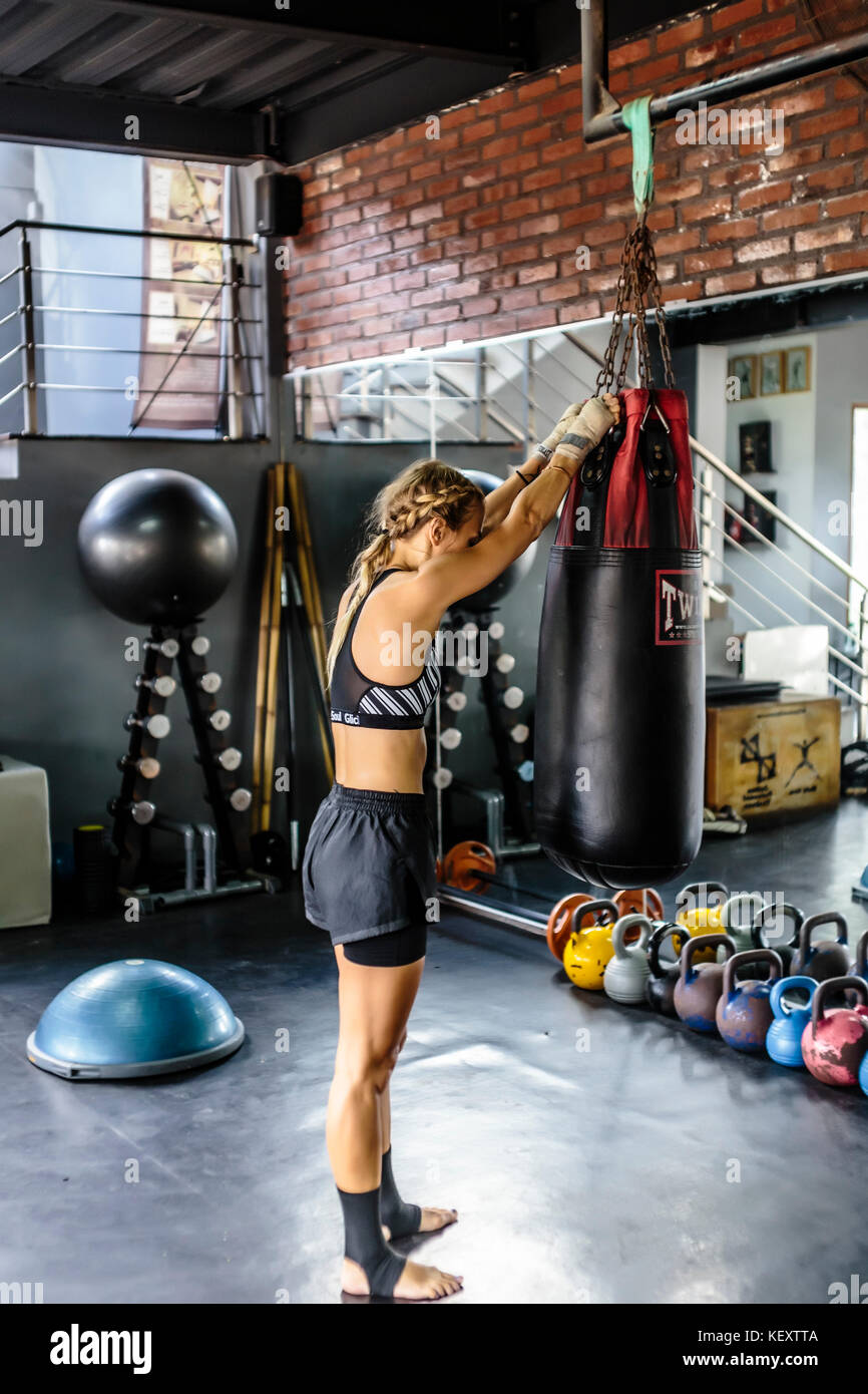 Photograph with side view of young woman hanging punching bag in kickboxing gym, Seminyak, Bali, Indonesia - Stock Image