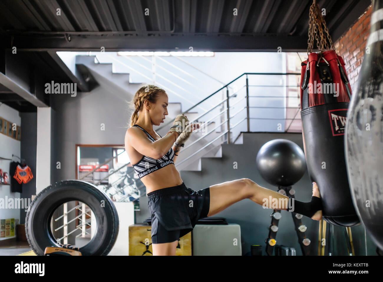 Side view photograph of female kickboxer kicking punching bag, Seminyak, Bali, Indonesia - Stock Image