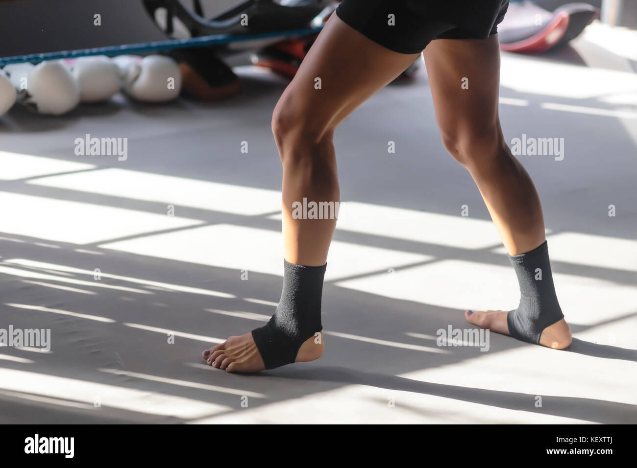 Photograph of young woman's legs in kickboxing stance, Seminyak, Bali, Indonesia - Stock Image
