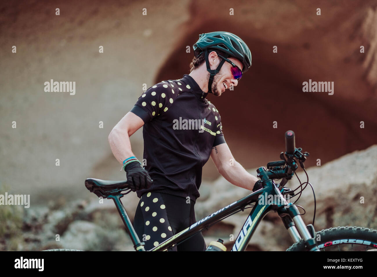 Man walking in desert with his mountain bike, Tenerife, Canary Islands, Spain Stock Photo