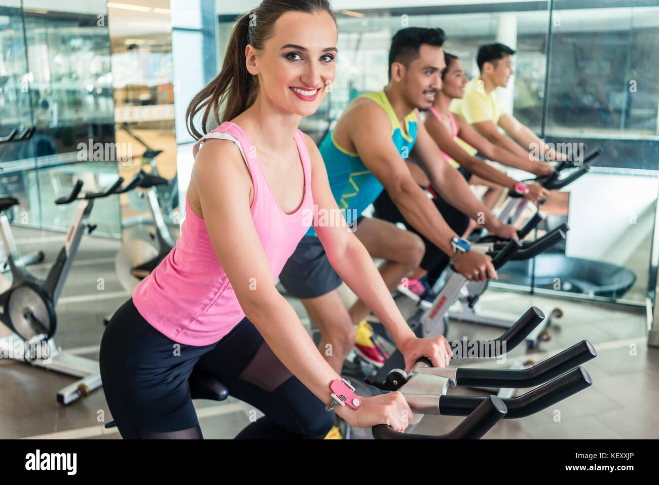 Beautiful fit woman smiling during cardio workout at indoor cycl - Stock Image