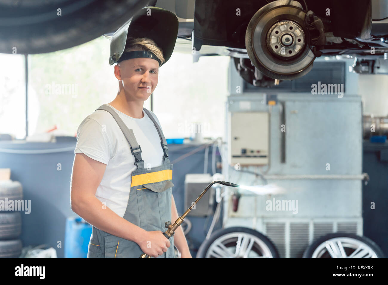 Portrait of a handsome auto mechanic looking at camera with conf - Stock Image