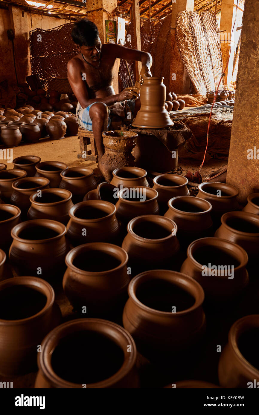Hands of making clay pot on the pottery wheel ,select focus, close-up. potter shaping up the terracotta clay pot on wheal, lady helpers in terracotta Stock Photo