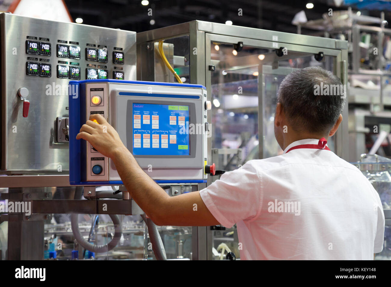 factory engineer controlling and pressing important technology button at control panel of an automatic machine in - Stock Image